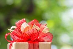 Caixa de presente amarrada com ouro e a fita vermelha Fotos de Stock