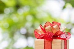 Caixa de presente amarrada com ouro e a fita vermelha Imagens de Stock