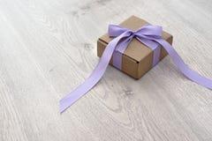 Caixa de presente amarrada com uma fita do roxo do cetim Foto de Stock