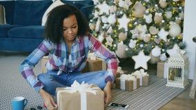Caixa de presente atrativa da embalagem da menina da raça misturada perto da árvore de Natal em casa video estoque