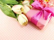 Caixa de presente atual e flores artificiais com fundo cor-de-rosa do às bolinhas Imagem de Stock Royalty Free