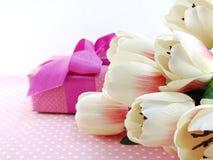 Caixa de presente atual e flores artificiais com fundo cor-de-rosa do às bolinhas Foto de Stock