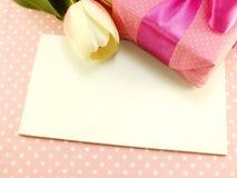 Caixa de presente atual e flores artificiais com fundo cor-de-rosa do às bolinhas Imagem de Stock