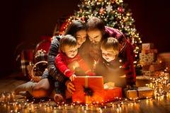 Caixa de presente atual leve aberta da família do Natal sob a árvore do Xmas, pai feliz Children da mãe imagens de stock royalty free
