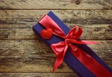 Caixa de presente azul com fita vermelha e coração pequeno Fotografia de Stock