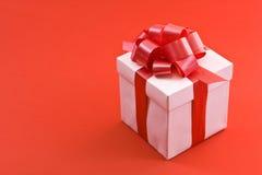 Caixa de presente branca com curva vermelha da fita do cetim Imagens de Stock