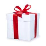 Caixa de presente branca com fita vermelha e a curva, isoladas no backgr branco Fotos de Stock Royalty Free