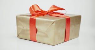 A caixa de presente de Brown amarrou a curva vermelha da fita isolada no fundo branco video estoque