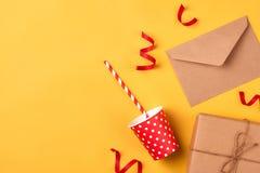 Caixa de presente, coisas da festa de anos e portátil em um backgroun amarelo Foto de Stock Royalty Free