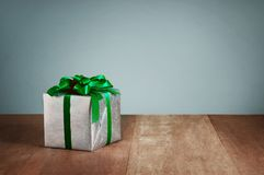 Caixa de presente com as fitas verdes no fundo de madeira Imagem de Stock Royalty Free