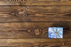 Caixa de presente com curva dourada na tabela de madeira Imagens de Stock