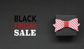 Caixa de presente com curva e texto de Black Friday no fundo preto ilustração stock