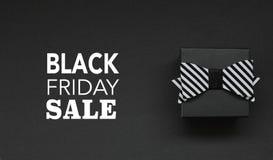 Caixa de presente com curva e texto de Black Friday no fundo preto ilustração do vetor
