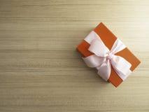 Caixa de presente com curva no fundo de madeira foto de stock royalty free