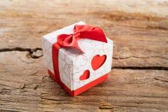 Caixa de presente com dois corações vermelhos no lado no fundo de madeira Foto de Stock