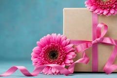 Caixa de presente com fita da curva e flores cor-de-rosa na tabela de turquesa Cartão para o dia do aniversário, da mulher ou de  Foto de Stock Royalty Free