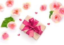 Caixa de presente com fita vermelha e curva no branco com fundo das flores lat liso, vista superior imagem de stock