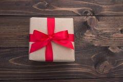 Caixa de presente com a fita vermelha na tabela de madeira para o dia de Valentim Fotos de Stock