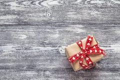 Caixa de presente com a fita vermelha nas placas de madeira pintadas preto-brancas fotos de stock