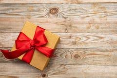 Caixa de presente com a fita vermelha no fundo de madeira, espaço da cópia, vista superior Imagem de Stock