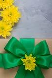 Caixa de presente com os crisântemos do amarelo da curva no backgro concreto cinzento Imagens de Stock Royalty Free