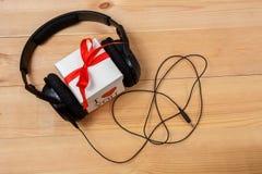 Caixa de presente com os fones de ouvido na tabela de madeira Imagem de Stock
