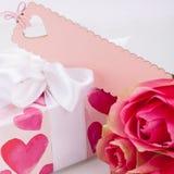 Caixa de presente com um Empty tag, ao lado de três rosas Fotos de Stock Royalty Free