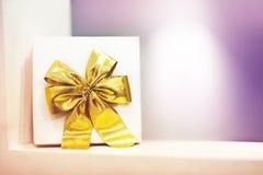 Caixa de presente com uma curva amarela em um fundo roxo imagem de stock