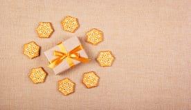 Caixa de presente com uma curva do ouro e biscoitos sob a forma dos flocos de neve Conceito do `s do ano novo Conceito do Natal C Fotos de Stock