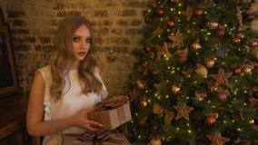 Caixa de presente da embalagem da menina perto da árvore de Natal em casa vídeos de arquivo