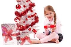 Caixa de presente da preensão da menina pela árvore de Natal Imagem de Stock Royalty Free
