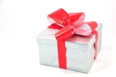 Caixa de presente de prata com a curva vermelha isolada no branco Imagens de Stock Royalty Free