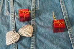 Caixa de presente de prata do coração em calças de brim para o fundo Imagens de Stock Royalty Free