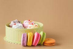 Caixa de presente de queques e de Macaron colorido no fundo bege, Imagens de Stock Royalty Free