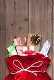 Caixa de presente de Santa Claus Bag Full By Present, saco vermelho do Natal no fundo de madeira velho da parede Fotografia de Stock Royalty Free
