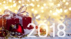 Caixa de presente de 2018 vermelhos na neve com fundo do bokeh Imagens de Stock Royalty Free