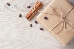 A caixa de presente decorou feijões e canela de café na tabela de madeira branca com espaço para o texto Imagens de Stock