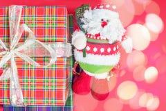 Caixa de presente do Natal com o brinquedo de Santa Claus no fundo vermelho Fotos de Stock Royalty Free