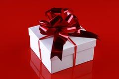 Caixa de presente do Natal com uma curva dark-red da fita Fotos de Stock
