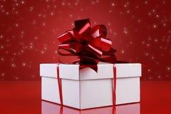 Caixa de presente do Natal com uma curva dark-red da fita Fotografia de Stock Royalty Free