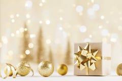 Caixa de presente do Natal contra o fundo dourado do bokeh Cartão do feriado imagens de stock