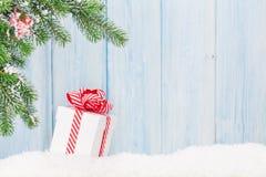 Caixa de presente do Natal e ramo de árvore do abeto na neve Imagem de Stock Royalty Free
