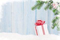 Caixa de presente do Natal e ramo de árvore do abeto na neve Fotos de Stock