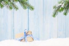 Caixa de presente do Natal e ramo de árvore do abeto na neve Imagens de Stock