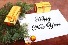 Caixa de presente do Natal em um desktop de madeira com letra para o espaço da cópia Imagem de Stock