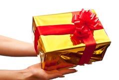 Caixa de presente do ouro na mão da mulher Fotos de Stock