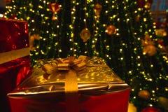 Caixa de presente do ouro sob a árvore de Natal Imagens de Stock