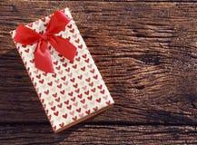Caixa de presente do presente do ponto do coração com a fita vermelha na textura de madeira velha Foto de Stock Royalty Free