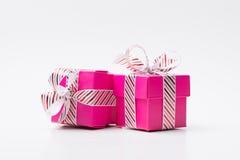 Caixa de presente dois cor-de-rosa amarrada com a fita vermelha branca da listra imagens de stock royalty free