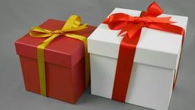 Caixa de presente dois no fundo cinzento A caixa de presente branca com curva vermelha da fita e a caixa de presente vermelha com video estoque